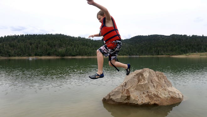 Eight-year-old Lucas Bohannan leaps from a rock into the chilly water of Grindstone Lake Thursday. The lake recently opened the lake to swimming and now rents kayaks and canoes.