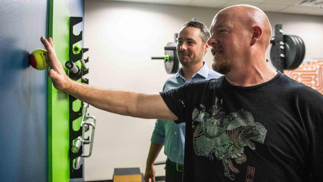 Sgt. Wade Fowler, right, a Williamson County Constable, is shown last year rolling a ball against a wall to help him address long-term shoulder pain. Dr. Ben Morgan, left, from the Texas Physical Therapy Specialists Clinic, has helped him to be pain-free without using medications.