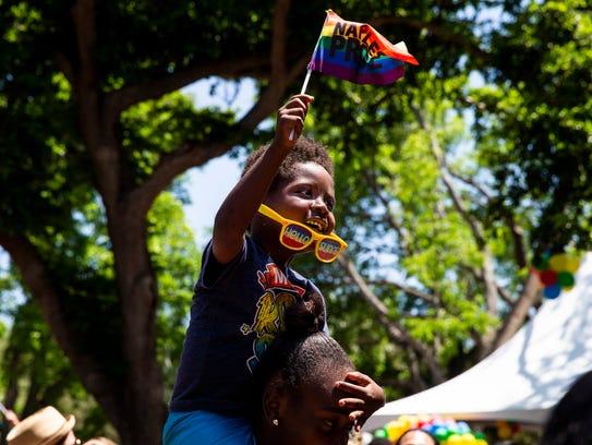 Sharon Simmons, 4, waves his Naples Pride flag while