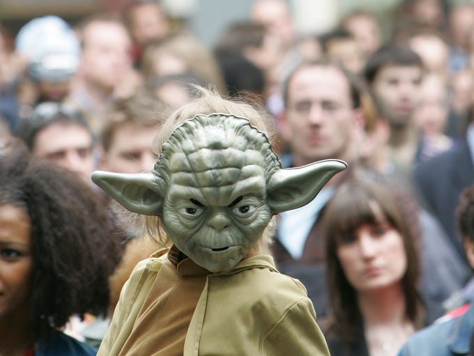 A young boy dressed as the Star Wars character 'Yoda'