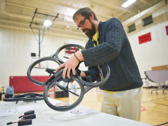 Roosevelt High School teacher Nathan Hofflander helps set up the drones before the Flight Club drone flying event Friday, Jan. 12, at the school in Sioux Falls. The Flight Club is for students interested in flying drones and the use of drones.