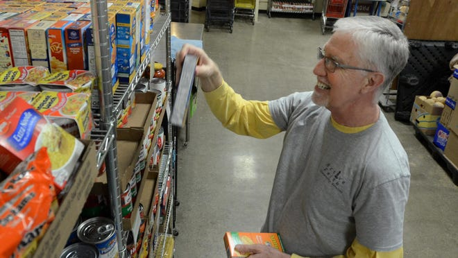 Active Faith volunteer John Ossenmacher stocks the shelves of the South Lyon food pantry on Monday.