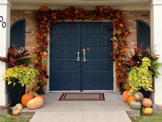 A garland and fall plants adorn the entrance of a home