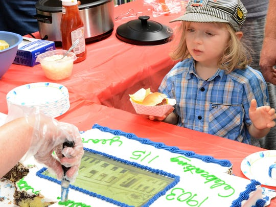 A young patron eyes up the perfect piece of cake at a celebration marking the 115th anniversary of the founding of Farnsworth Public Library in Oconto.