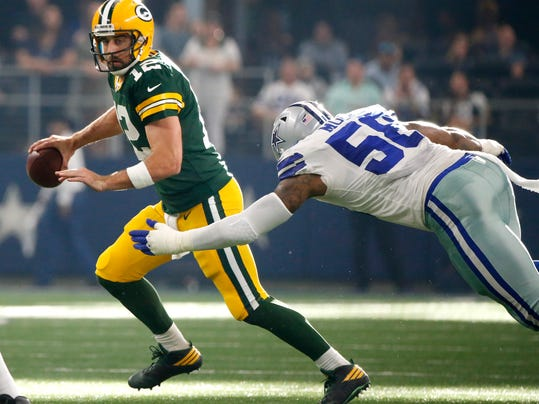 Green Bay Packers quarterback Aaron Rodgers (12) scrambles away from Dallas Cowboys defensive end Damontre Moore (58) in the second half of an NFL football game, Sunday, Oct. 8, 2017, in Arlington, Texas. (AP Photo/Michael Ainsworth)