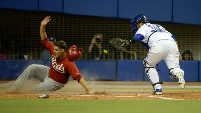 Cincinnati Reds outfielder Steven Selsky scores a run as Toronto Blue Jays catcher Dioner Navarro drops the ball in the eighth inning at Olympic Stadium in April of 2015.