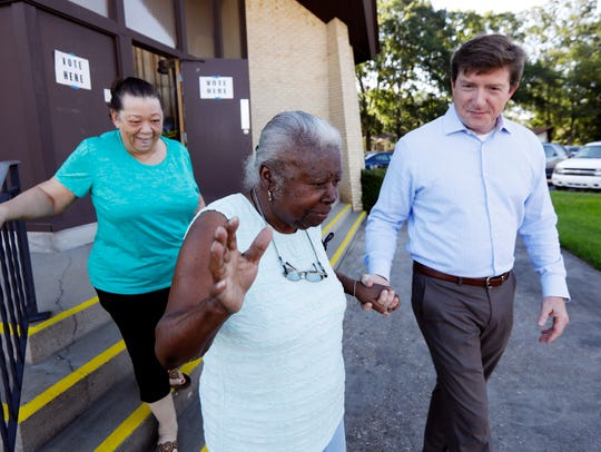 State Rep. David Baria, D-Bay St. Louis, helps a woman
