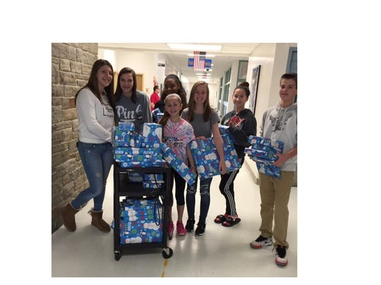 Elves from Lakeside Middle School's chapter of the National Junior Honor Society are ready to deliver presents to the family they adopted for the holiday season.