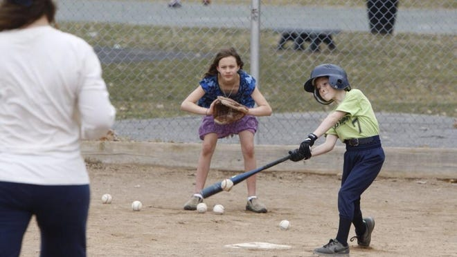 Aren Hotaling, 8, rips a pitch off mom Lisa Hotaling as sister Asha catches on a warm day at Cobbs Hill Park. Cold is moving into the area, though.