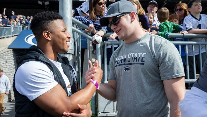 Former Penn State running back Saquon Barkley, left, talks with letterman Carl Nassib during the Blue-White spring college football game Saturday, April 21, 2018, in State College, Pa.