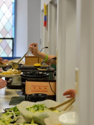 A volunteer ladles gravy onto a plate of food at First Presbyterian Church in Manitowoc on Wednesday, May 25. The church hosts dinners each Wednesday that are free and open to the public. Tonight, volunteers fed 69 people from the community.
