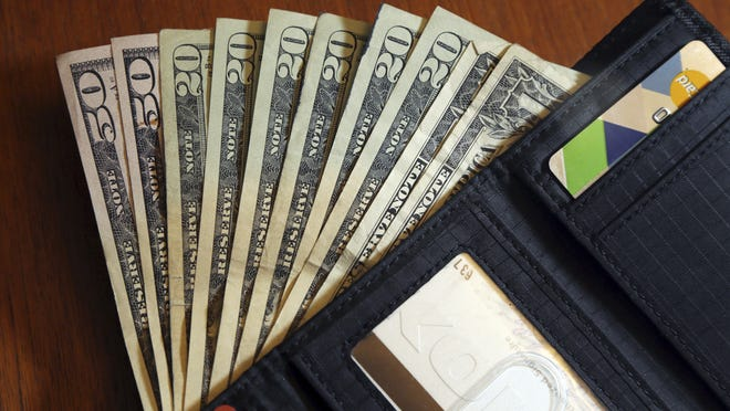 Cash is fanned out from a wallet in North Andover.