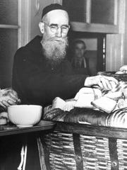 Father Solanus Casey of Detroit serves bread in 1942.