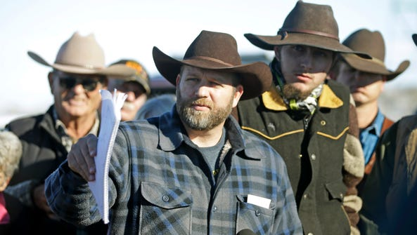 Ammon Bundy, center, speaks with a reporter at a news