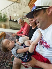Bobby Harrison holds his 2-year-old daughter Hope at the Medoffs' home. Hope was born with Trisomy 18 chromosomal anomaly. Looking on is Harrison's wife Rachel and his father-in-law Mark Medoff.