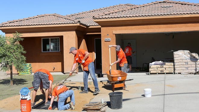 Volunteers from Home Depot finish the front yard of a home in partnership with the Coachella Valley Housing Coalition in Coachella, Wednesday, Sept. 16, 2015.
