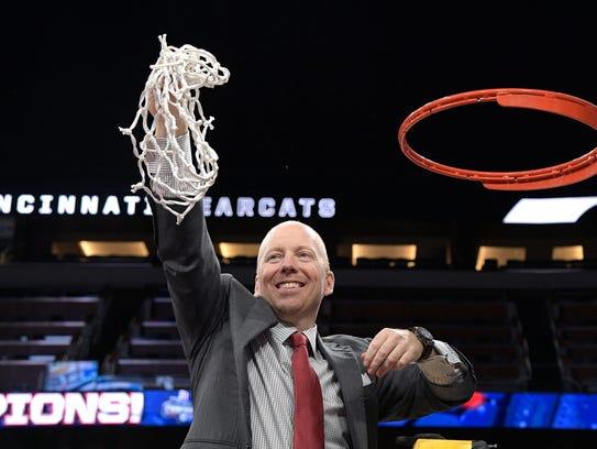 Cincinnati head coach Mick Cronin holds the net toward