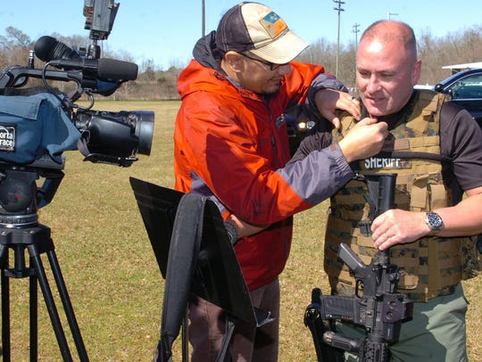 A videographer mike's up Capt. Clay Higgins for an