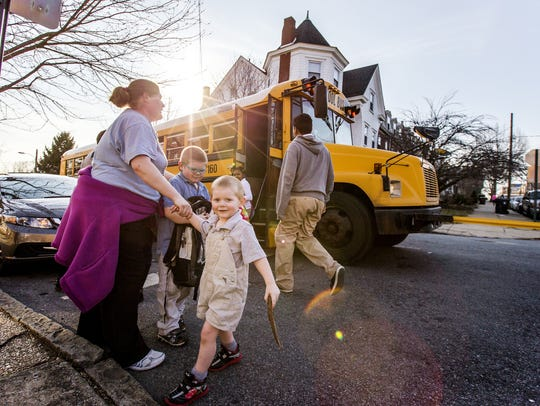 Children get off a school bus at West Seventh and North