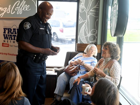 Jackson Police Department Captain Derick Tisdale talks with customers at Starbucks Coffee, Wednesday afternoon during AARP of West Tennessee's Coffee with Cops.
