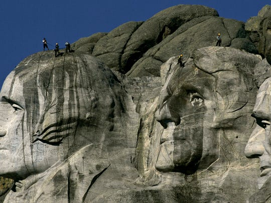 In this July 22, 2005 file photo, water streaks down the faces of presidents George Washington, left, and Thomas Jefferson, center, as workers pressure wash Mount Rushmore National Memorial in South Dakota.