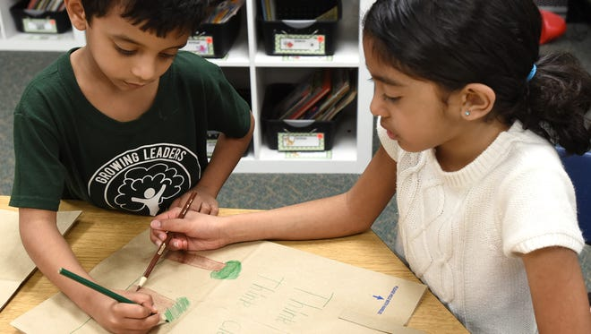 Deerfield Elementary School students Shushruth Kurubas (left) and Lakshmi Vivesen work on adding ecological messages to Kroger grocery bags April 13.