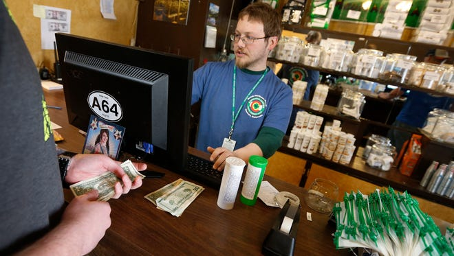 A customer pays cash for retail marijuana at 3D Cannabis Center in Denver on May 8.