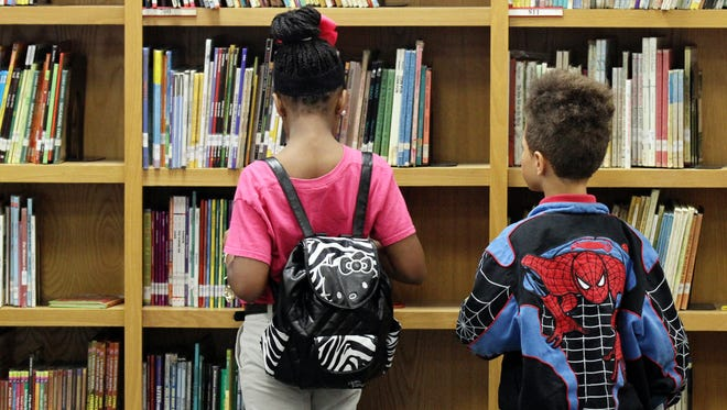 Students look through books in the school library Friday, May 2, 2014, at J.W. Faulk Elementary in Lafayette, La.