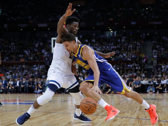 Golden State Warriors' Klay Thompson, right, drives