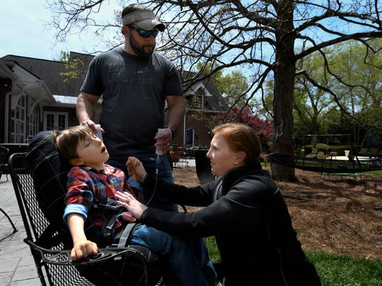 Stefanie Dean Brown and her husband Jason, give their son Dean 7, who has cerebral palsy, some water at their home Saturday, April 21, 2018, in Nashville, Tenn. Brown calls her son her guardian angel. The birth of Dean helped doctors discover that Stefanie has a rare cancer, LAM, which stands for lymphangioleiomyomatosis.
