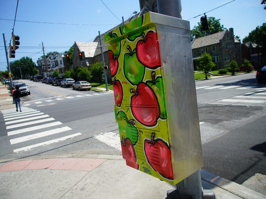 Apples are painted on an electrical box at North Rodney and Fourth streets in Wilmington by an artist working with West Side Grows Together, a revitalization organization that is trying to beautify and encourage healthy life styles.