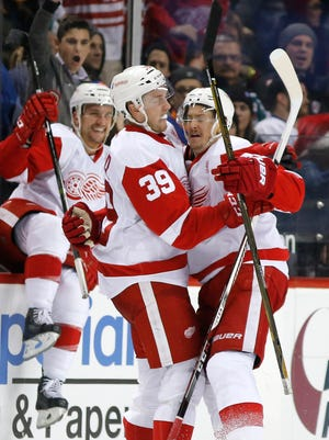 Detroit Red Wings' right wing Anthony Mantha (39) celebrates with Red Wings' defenseman Danny DeKeyser, right, after DeKeyser scored the winning goal during overtime.