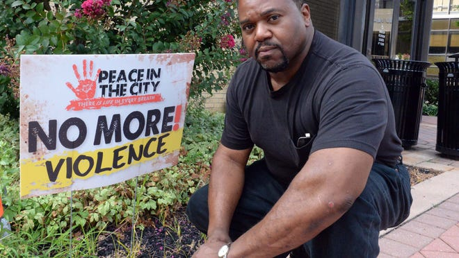 Millville Commissioner David Ennis is seen with a message of peace sign that he recently posted in front of the city municipal building on Friday, August 22, 2014. Ennis, a pastor at In His Presence church, is planning a Peace in the City for September.