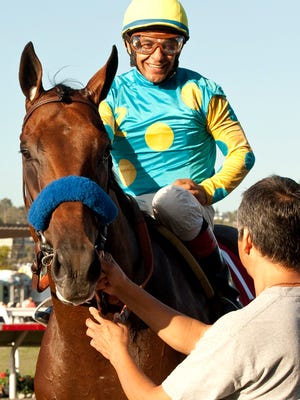 Zayat Stables' American Pharoah and jockey Victor Espinoza are guided into the winner's circle after their victory in the Grade I, $300,000 Del Mar Futurity in September