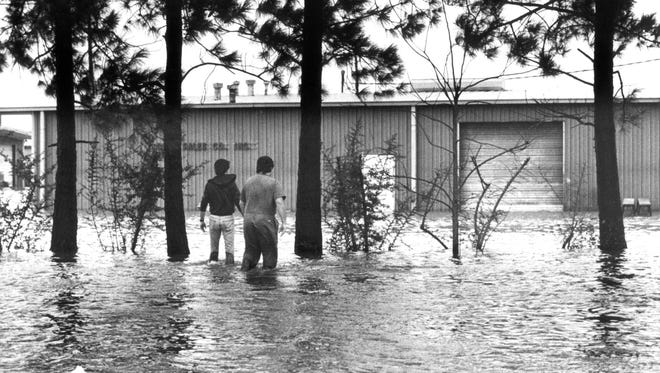 Martin Jenson and Gary Netherland wade water on Dec. 27, 1982, behind Kilpatrick Funeral Home on North Seventh Street in West Monroe to reach the business they worked for, Home Exteriors, in that area.