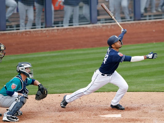 San Diego Padres' Fernando Tatis watches a home run in front of Seattle Mariners catcher Tuffy Gosewisch during the eighth inning of a spring training baseball game Friday, Feb. 23, 2018, in Peoria, Ariz. (AP Photo/Charlie Neibergall)