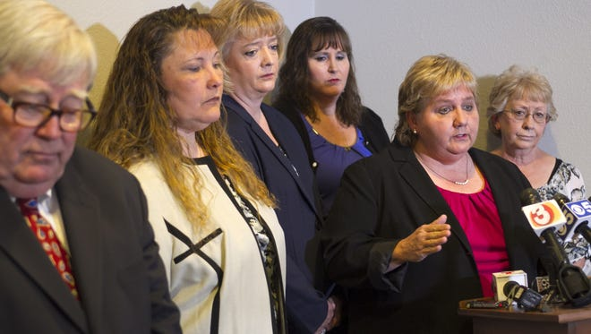 Deborah Harper, speaks as, from left, Michelle Parker, Tracey Everitt, Jana Leineweber and Janet Sabol listen during a press conference at their attorney's office in Phoenix in 2014.