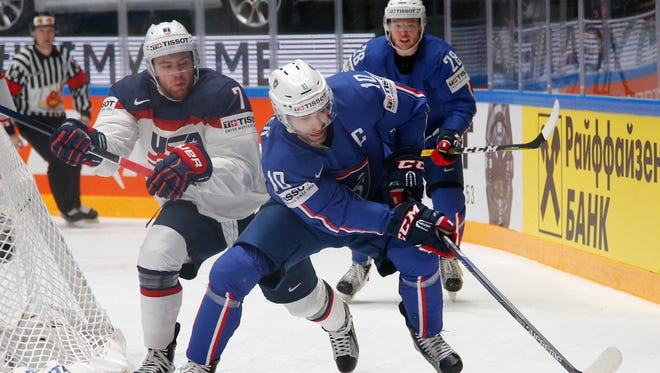 J.T. Compher, left, of the United States, fights for the puck with France''s Laurent Meunier during the hockey world championships  in St. Petersburg, Russia, on Thursday, May 12, 2016.