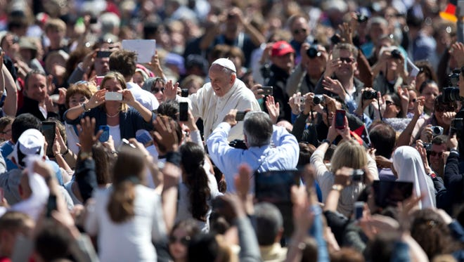 Pope Francis greets the faithful after celebrating an Easter Sunday Mass in St. Peter's Square at the Vatican Sunday, April 20, 2014. Cheering and applauding, the crowd tried to catch a glimpse of the pontiff as he circled around in his white popemobile at the end of the ceremony before he went to the central balcony over the basilica to deliver his commentary on the violence and poverty staining the Earth.(AP Photo/Andrew Medichini)