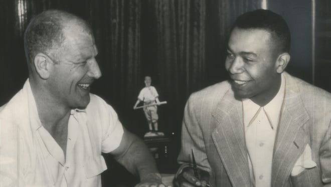 The second African-American player to get into the major leagues and the first in the American League, Larry Doby (right) signs a Cleveland contract on July 5, 1947, in Chicago with Bill Veeck, president of the Indians. He made his debut that afternoon as a pinch hitter and struck out. This photo was published in the July 7, 1947, Milwaukee Journal.