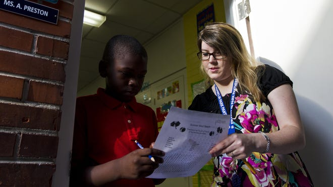 Amanda Preston, a new teacher at Franklin Park Elementary school in Fort Myers, helps one of her students work on a daily word exercise Monday morning.