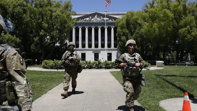 Members of the California National Guard walk the grounds near the Jesse M. Unruh State Office building in Sacramento on June 2. Gov. Gavin Newsom's administration announced it cost more than $24 million to deploy 8,000 National Guard members for 18 days during the recent protests of racial injustice inspired by the death of George Floyd on May 25 in Minneapolis.