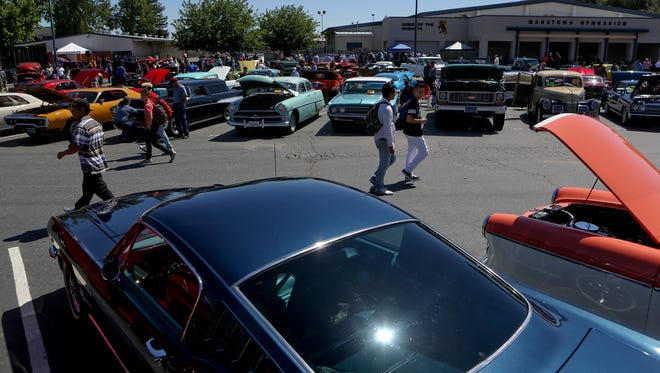 Car enthusiasts and Enterprise High School students walk through the parking lot during a Kool April Nites show 'n' shine Friday at the school in Redding.
