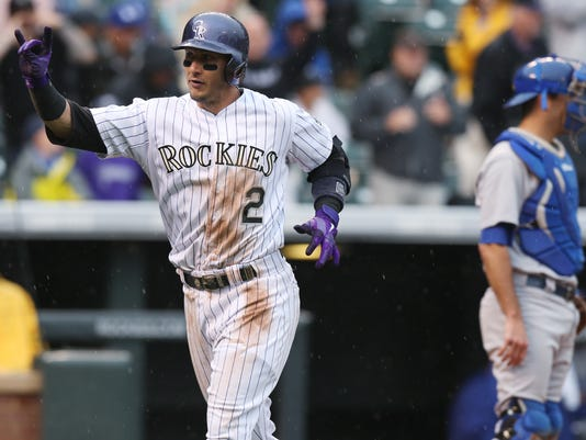 Colorado Rockies' Troy Tulowitzki, front, gestures as he crosses home plate after hitting a solo home run as Los Angeles Dodgers catcher Drew Butera looks on in the fourth inning of a baseball game in Denver on Sunday, June 8, 2014. (AP Photo/David Zalubowski)