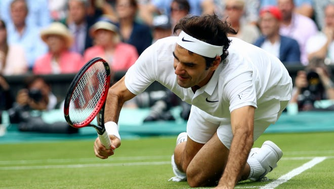 Roger Federer of  falls over during his men's semifinal singles match against Milos Raonic  on Friday.
