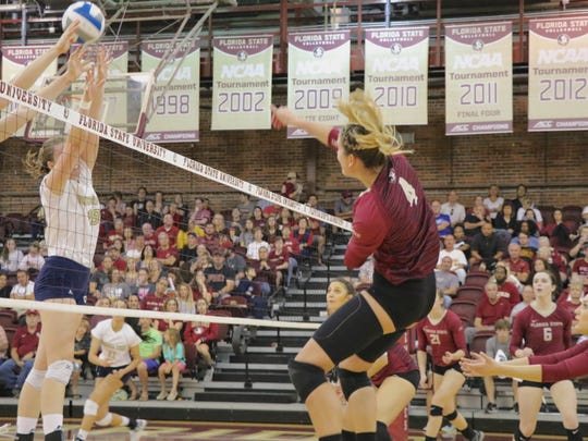 Katie Horton (4) smacks an attempted kill at the Yellow Jackets wall of defense during Florida State's 3-2 victory against Georgia Tech at Tully Gymnasium on Friday, November 25th, 2016.