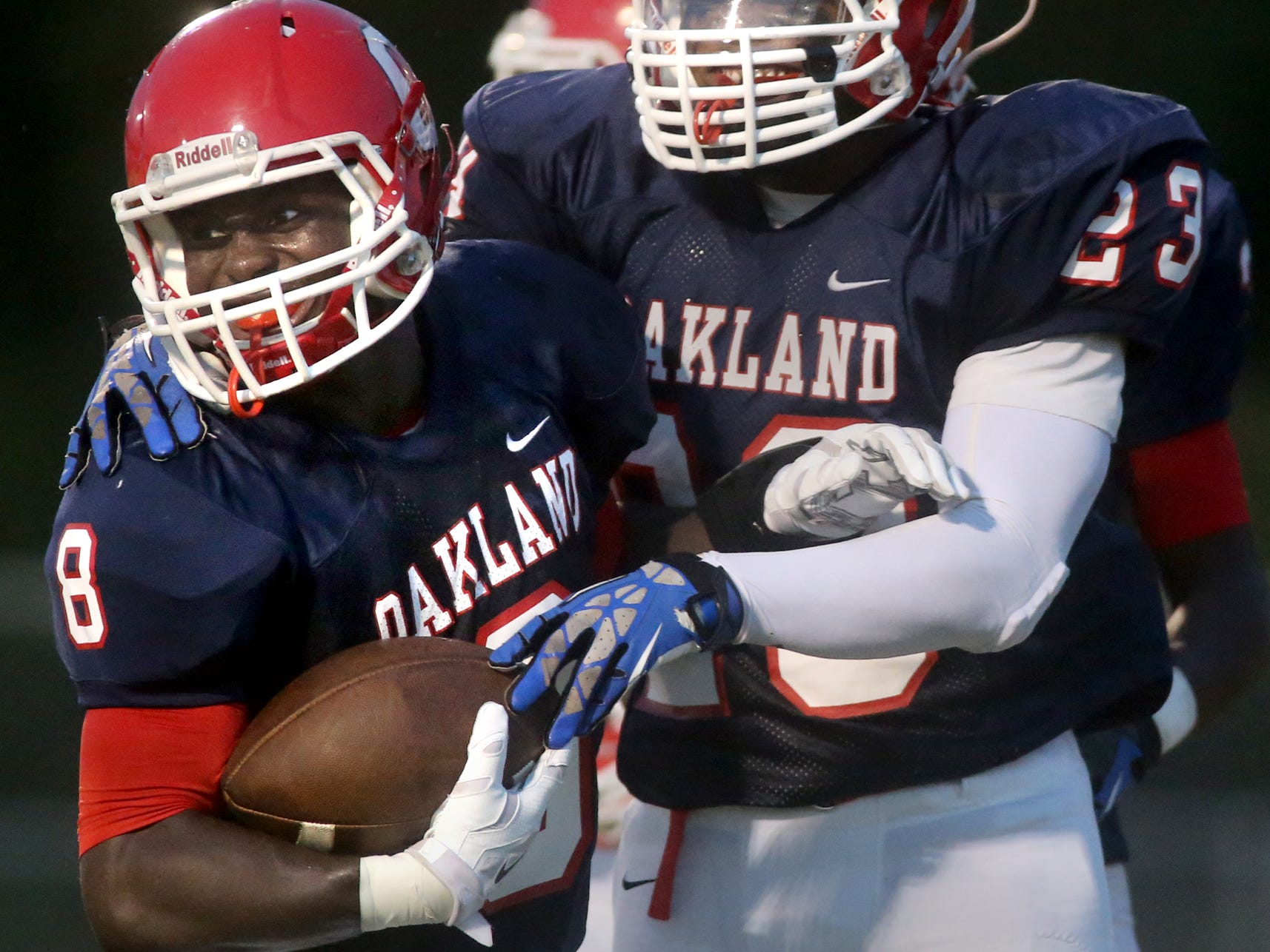 Oakland's George Gbesee is congratulated by teammate Turrel Ward after Gbeseea scored a touchdown from a recovered fumble in the first half of the game against White Station at Oakland, on Friday, August 2, 2014.