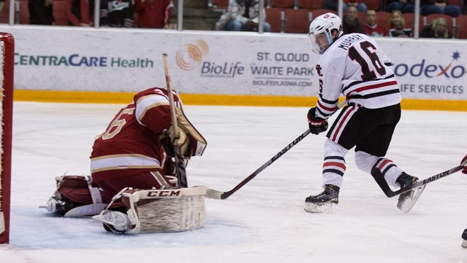St. Cloud State's Jimmy Murray (16) watches Denver goalie Tanner Jaillet make a save Friday at the Herb Brooks National Hockey Center.