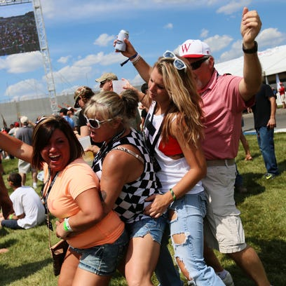 A group of people danced in a line Friday at the Turn 4 Infield Stage during O.A.R.'s performance at the Indianapolis Motor Speedway.