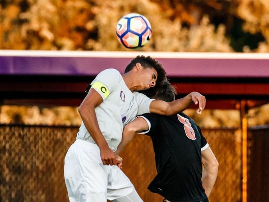 Oconomowoc senior Cameron Briggs (left) battles for a header during the match at home against Verona on Tuesday, Aug. 22, 2017.